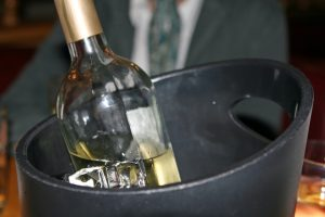 White wine bottle in an ice bucket, macro close up with copy space